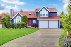 有白色修剪和好的草坪的大蓝色房子 免版税库存图片