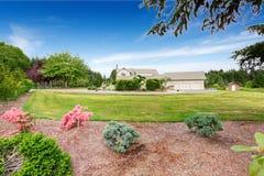 有白色修剪的大米黄房子和保管妥当的草坪 库存图片