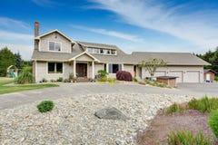 有白色修剪的大米黄房子和保管妥当的草坪 免版税图库摄影