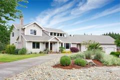 有白色修剪的大米黄房子和保管妥当的草坪 免版税库存图片