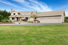 有白色修剪的大米黄房子和保管妥当的草坪 图库摄影