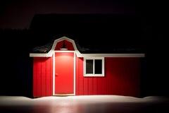 有白色修剪的小红色谷仓在冰冷的雪 库存图片