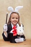 有白色兔宝宝的愉快的魔术师女孩在帽子 免版税图库摄影
