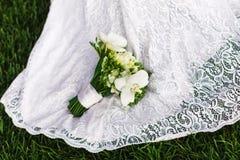 有白色兰花花束的新娘在婚礼礼服的 免版税库存图片