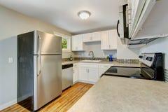 有白色内阁和钢装置的用装备的厨房室 免版税库存图片