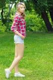 有白色卷发大嘴唇的美丽的性感的女孩有构成的在运动鞋有短裤的和衬衣的清洁站立在cag 免版税库存图片