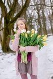 有白色和黄色郁金香花束的美丽的女孩在公园 库存照片