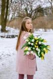 有白色和黄色郁金香花束的美丽的女孩在公园 图库摄影