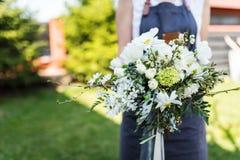 有白色和绿色花束的现代卖花人 库存照片