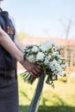 有白色和绿色花束的现代卖花人 库存图片
