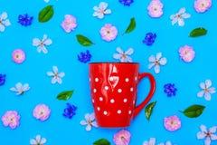 有白色圆点的陶瓷红色杯子在蓝色背景 库存照片