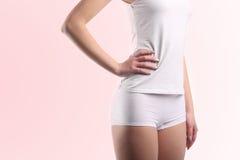 有白色在桃红色隔绝的棉花内裤和衬衣的少妇身体 库存照片