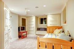 有白色墙壁和地毯的干净和明亮的地下室卧室。 免版税图库摄影