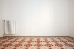 有白色墙壁和砖地的空的室与花卉装饰 免版税库存图片