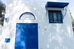 有白色墙壁和蓝色窗口门的突尼斯东部庭院房子 库存图片