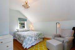 有白色墙壁和黄色地毯的舒适顶楼卧室 免版税库存图片
