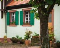有白色墙壁的一个传统德国房子、绿色快门和瓦屋顶、一个围场有花盆的和一棵树在它附近 免版税图库摄影