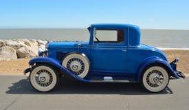 有白色墙壁轮胎的葡萄酒蓝色机动车在沿海岸区散步停放了 库存图片