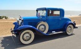 有白色墙壁轮胎的葡萄酒蓝色机动车 库存图片
