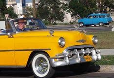 有白色墙壁轮胎的经典黄色汽车在哈瓦那 图库摄影