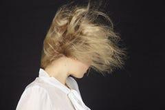 有白色女衬衫的金发的妇女在风暴(风力机) 免版税库存图片