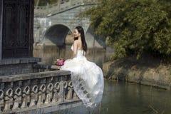 有白色婚礼礼服的一名妇女在shui上海bo公园运载新娘花束坐一间修道院 免版税库存图片