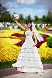 有白色婚礼花束的愉快的新娘 免版税图库摄影