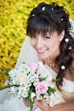 有白色婚礼花束的愉快的新娘 免版税库存照片