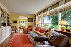 有白色存贮和红色地毯的客厅 免版税库存图片