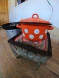 有白色小点的红色平底锅在一个老火炉 免版税库存照片