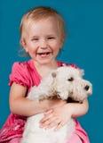 有白色小狗的笑的女孩 免版税图库摄影