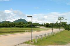 有白色尖桩篱栅和蓝色多云天空的弯曲的路 免版税图库摄影