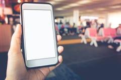 有白色屏幕的巧妙的电话在手中在被弄脏的位子机场背景 库存图片