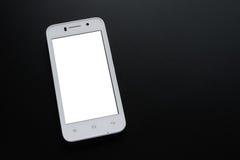 有白色屏幕的白色巧妙的电话在黑表上 库存图片