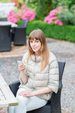 有白色巧妙的电话的愉快的美丽的年轻studient女孩户外在度假微笑的发短信和 她看 图库摄影