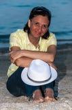 有白色帽子的被晒黑的妇女 免版税库存照片