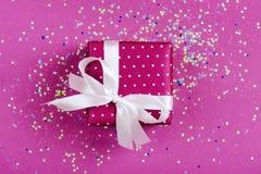有白色弓的当前箱子在与多彩多姿的五彩纸屑的桃红色背景 库存图片