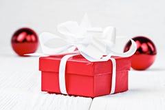 有白色弓的红色圣诞节礼物盒在白色木桌上 免版税库存图片