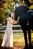 有白色新娘礼服的时兴的夫人在棕色马附近本质上 摆在与马的一件长的礼服的美丽的少妇 库存照片