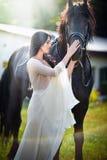有白色新娘礼服的时兴的夫人在棕色马附近 摆在与一匹友好的马的一件长的礼服的美丽的少妇 免版税库存图片
