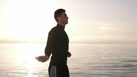 有白色无线耳机的高,肌肉年轻人行使与跳绳的在海边 年轻人订婚  影视素材