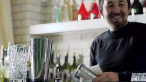 有白色旧布的愉快的男性侍酒者清洁振动器和在酒吧柜台上把它放在空的玻璃旁边在咖啡馆 股票视频