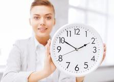 有白色时钟的可爱的女实业家 库存照片