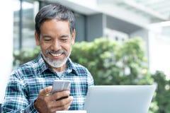 有白色时髦的短的胡子的微笑的愉快的成熟人使用智能手机小配件室外咖啡店的咖啡馆的服务互联网 图库摄影