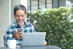 有白色时髦的短的胡子的微笑的愉快的成熟人使用智能手机小配件服务互联网 库存图片