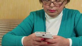 有白色智能手机的妇女 在她的手机的妇女键入的sms 股票视频