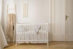 有白色木小儿床的,与拷贝空间的真正的照片斯堪的纳维亚托儿所 库存照片