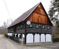 有白色木底部的老用木材建造的房子 库存图片