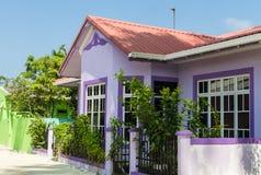 有白色木窗口的紫色房子在反对蓝天的一个红色屋顶下 库存图片