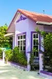 有白色木窗口的紫色房子在反对蓝天的一个红色屋顶下 免版税库存图片